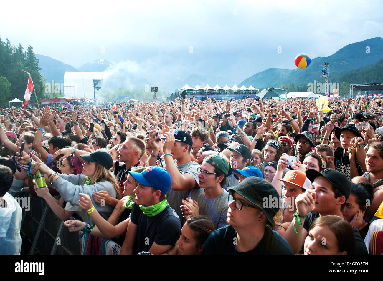 Huge crowds the outdoor rock concerts.  Fans cheer in the rain at the Pemberton Music Festival.  Pemberton BC, Canada - Stock Image
