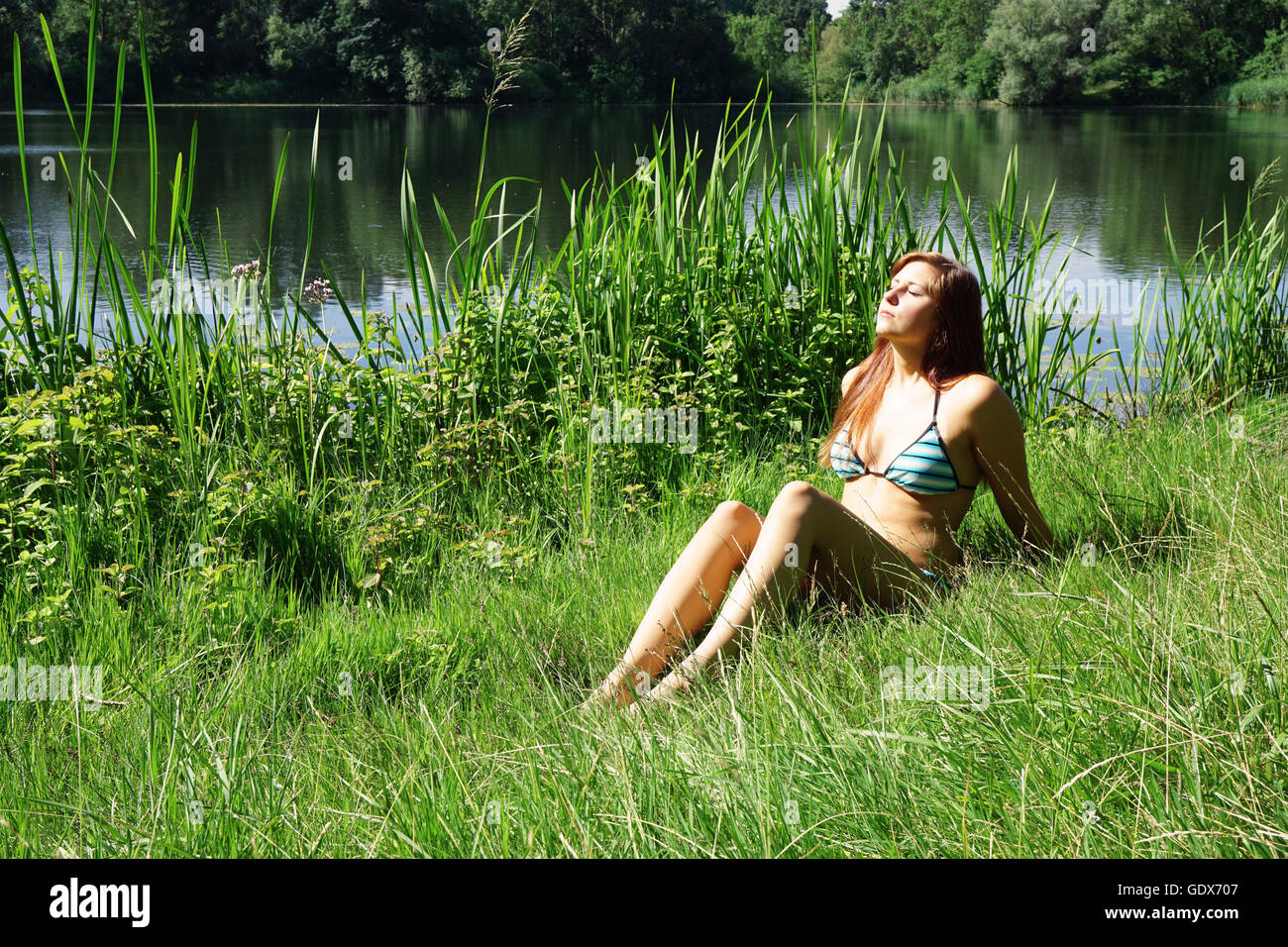 young woman basking in the sun - Stock Image