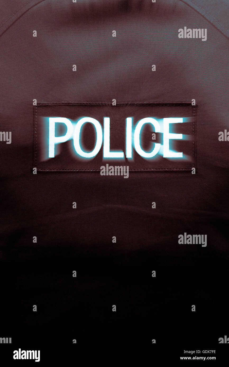Policeman seen from behind  with Police stab vest bearing the word 'Police' in bold lettering - Stock Image