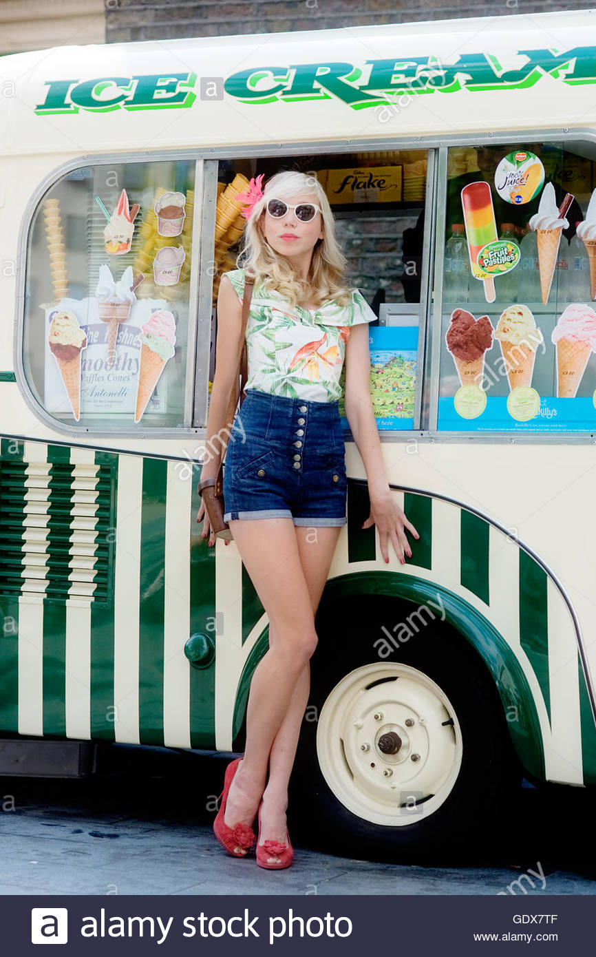 Woman wearing a vintage Hawaii shirt and denim shorts leans against a traditional 50s style ice cream van, London - Stock Image
