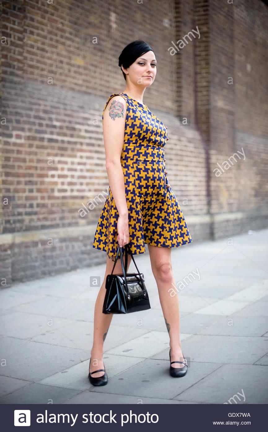 Woman wearing vintage hounds-tooth dress York Way Kings Cross London England UK. - Stock Image