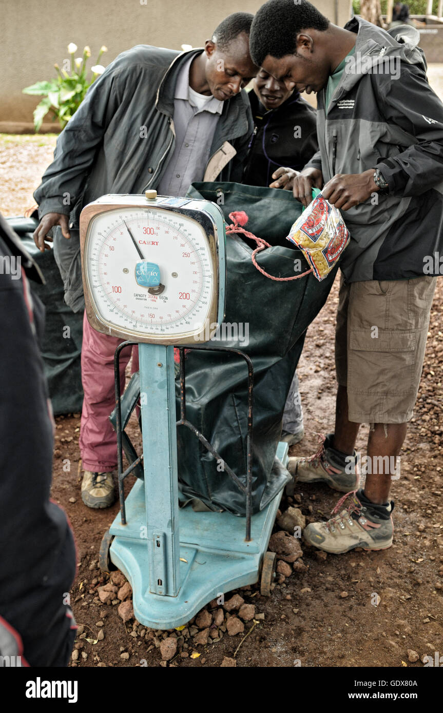Porters weighing in their loads at Londorossi Gate, Mount Kilimanjaro National Park, Tanzania - Stock Image
