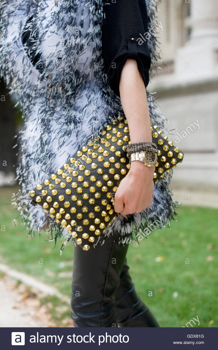 Detail of fashion designer Janina Nectara, wearing a belted faux fur, with glitzy  gold studded clutch. - Stock Image