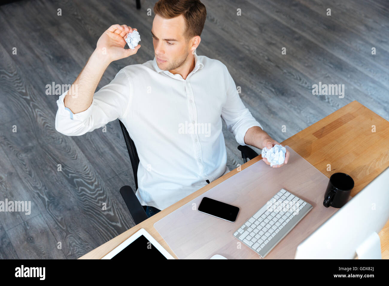 Top view of serious young businessman throwing crumpled paper and working in office - Stock Image