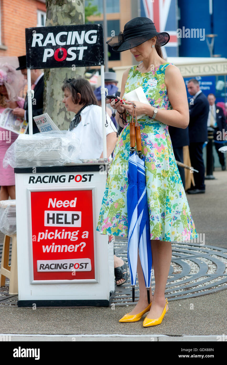 A day at the Races.Woman arriving for Royal Ascot Ladies day next to a Racing Post newspaper stand, Berkshire, England - Stock Image