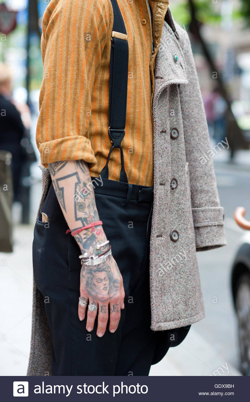 Detail of Model Jiimmy Q with  Tattoos shirt and braces, during London Fashion Week. - Stock Image