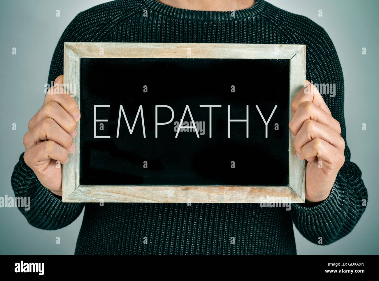 closeup of a young caucasian man showing a chalkboard with the text empathy written in it - Stock Image