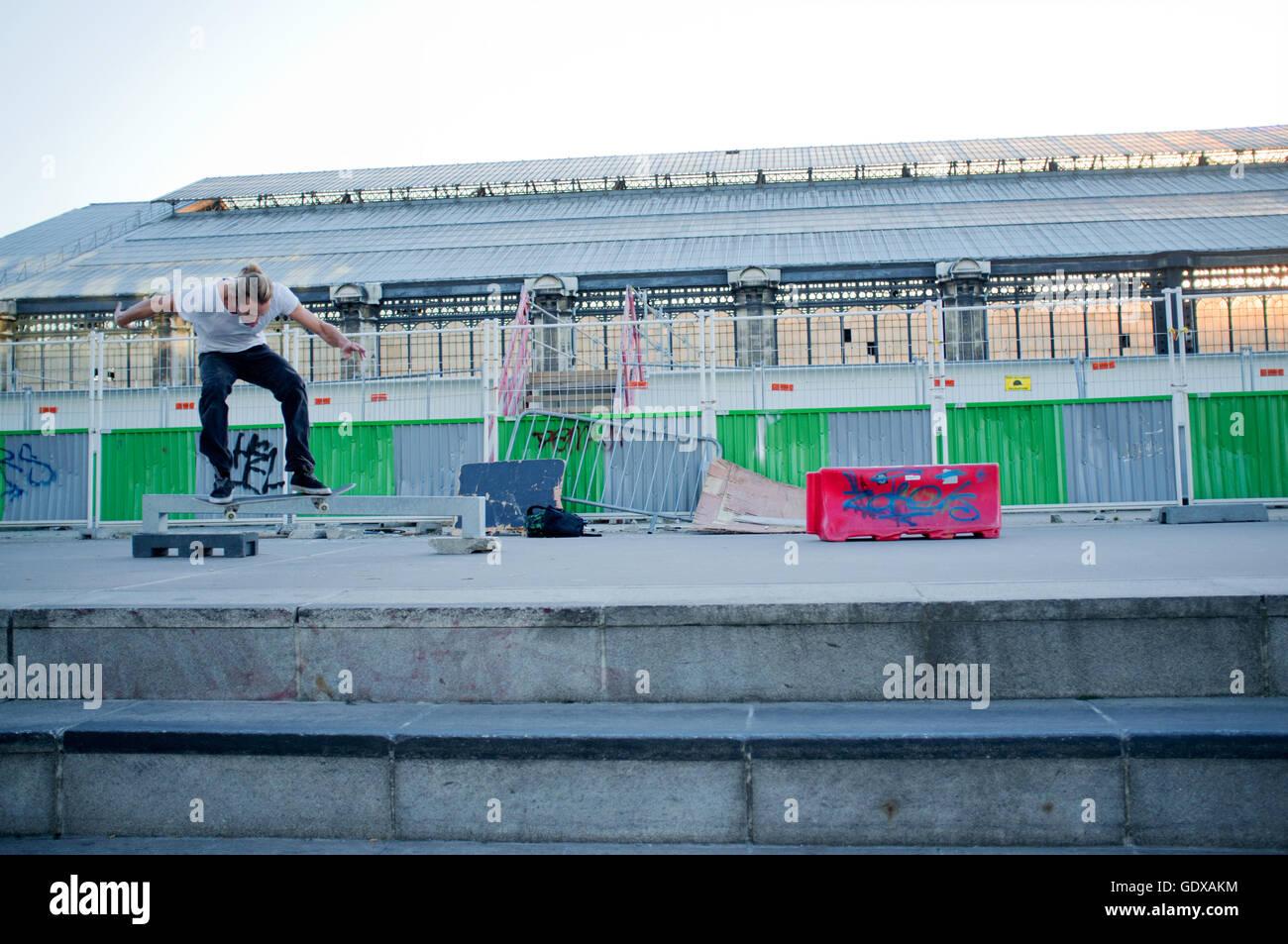 Airborne Skateboarder jumps in front of Gard d' Austerlitz, Paris. - Stock Image