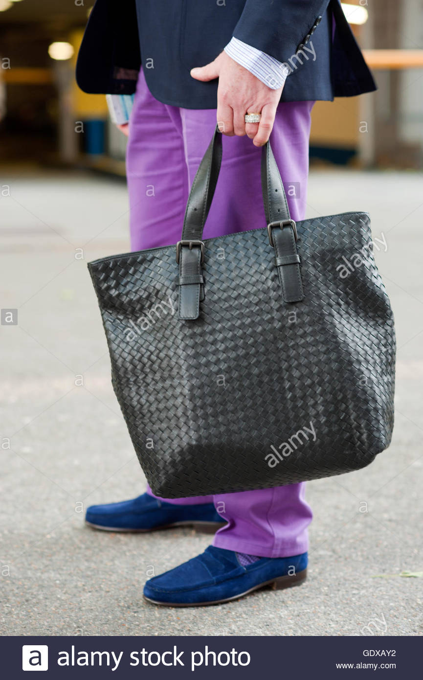 Detail,of David Furnish with bag accessory wearing purple jeans, London, LFW. - Stock Image