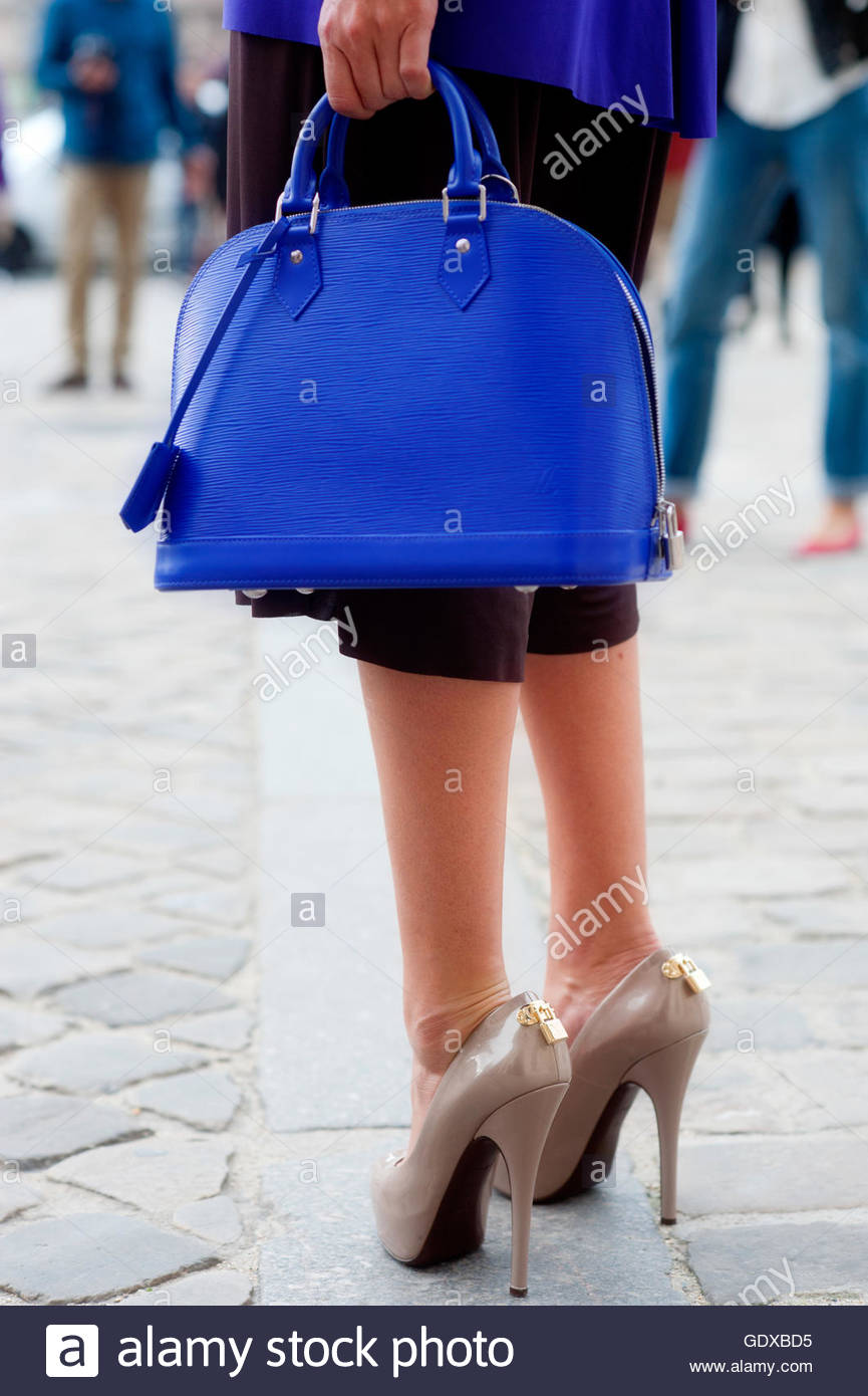 Detail, legs and tote handbag of Virgina Courtin Clarins after Louis Vuitton Fashion Show, at the Cour Carrée - Stock Image