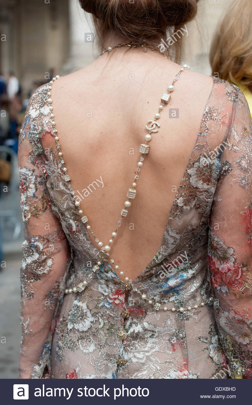 Rear detail of  a woman wearing a Couture dress. Shot during Paris Haute Couture Fashion Week. - Stock Image