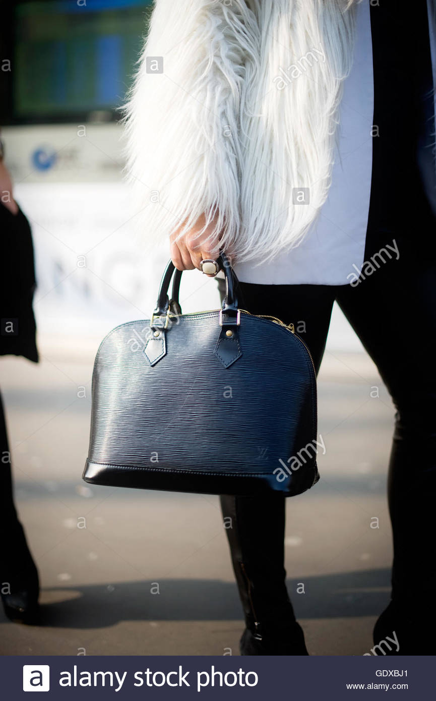 Mono contrast. Detail of womens tote bag worn with white fur at the Jardin des tuileries, during Paris Fashion Week. - Stock Image