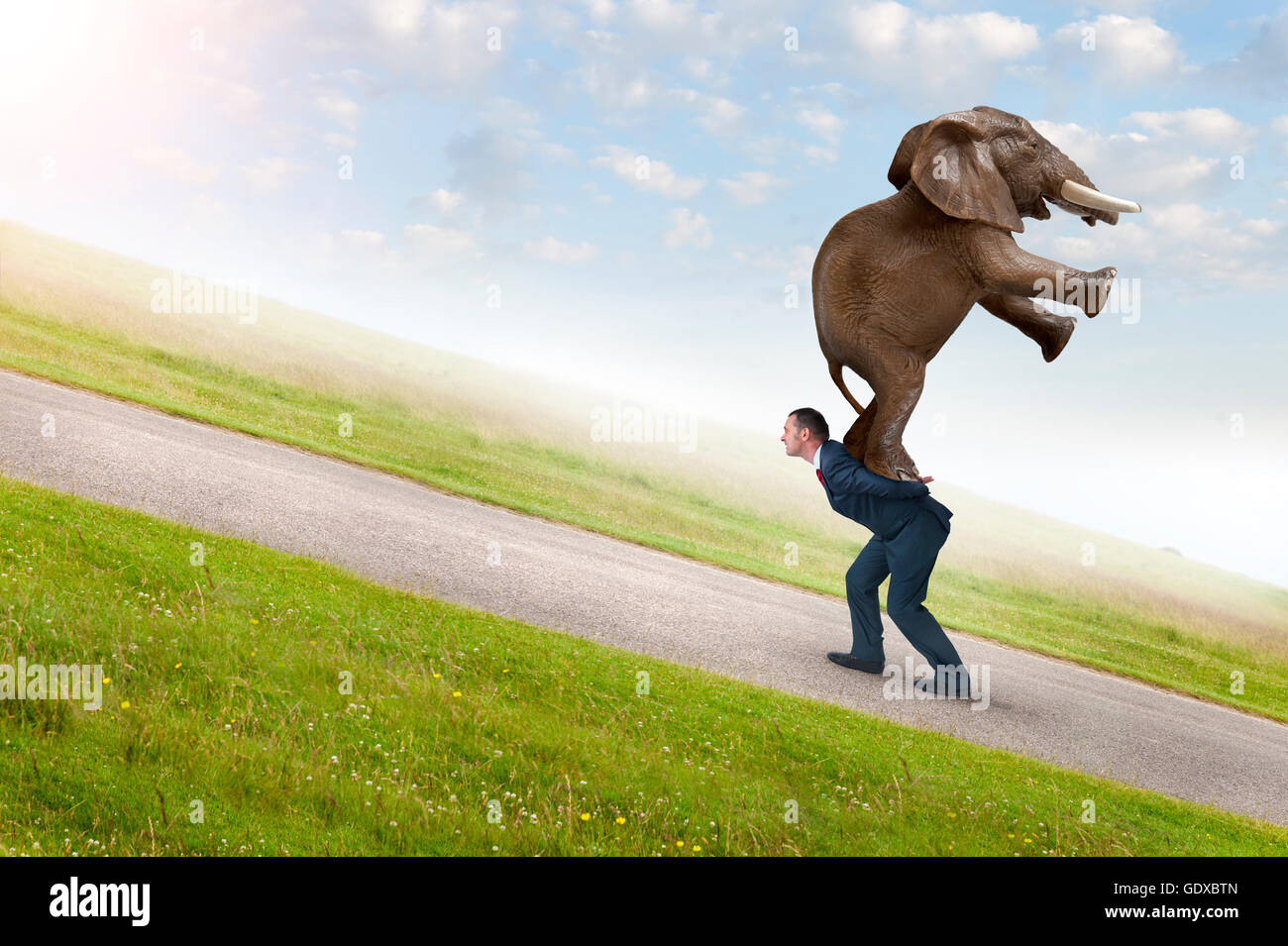 business adversity concept with businessman carrying elephant uphill - Stock Image