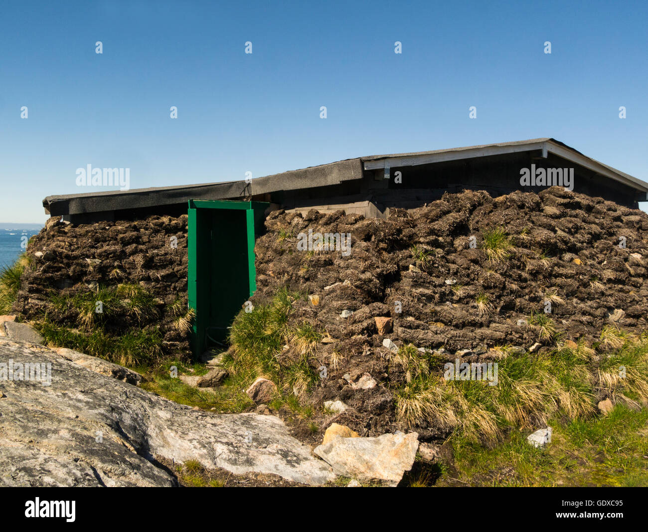 Turf peat house used by Inuits as winter home Ilulissat is a town in Qaasuitsup municipality in western Greenland - Stock Image