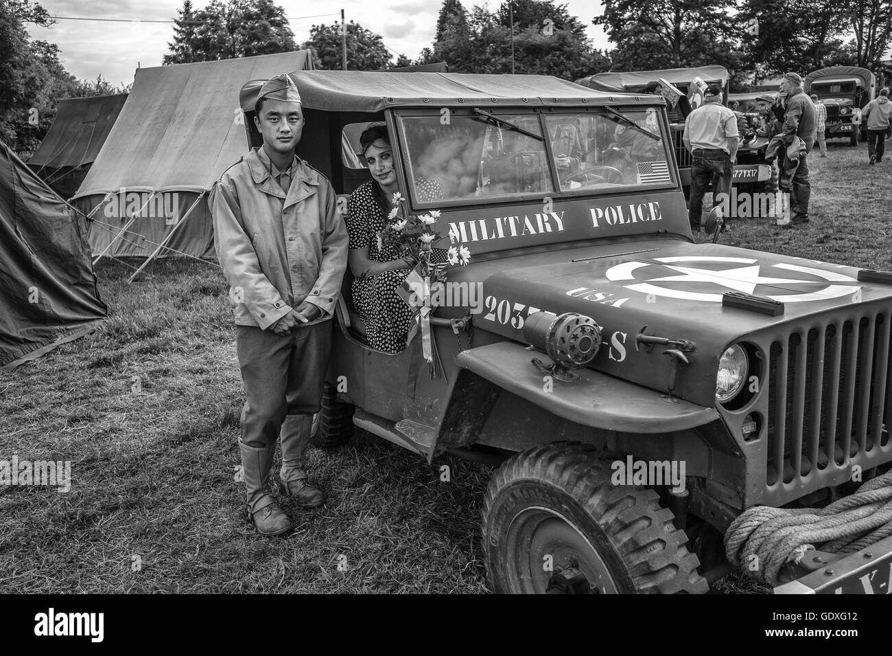 Man and woman pose next to a Willys Jeep at the D-Day reenactment in France, 2014 - Stock Image