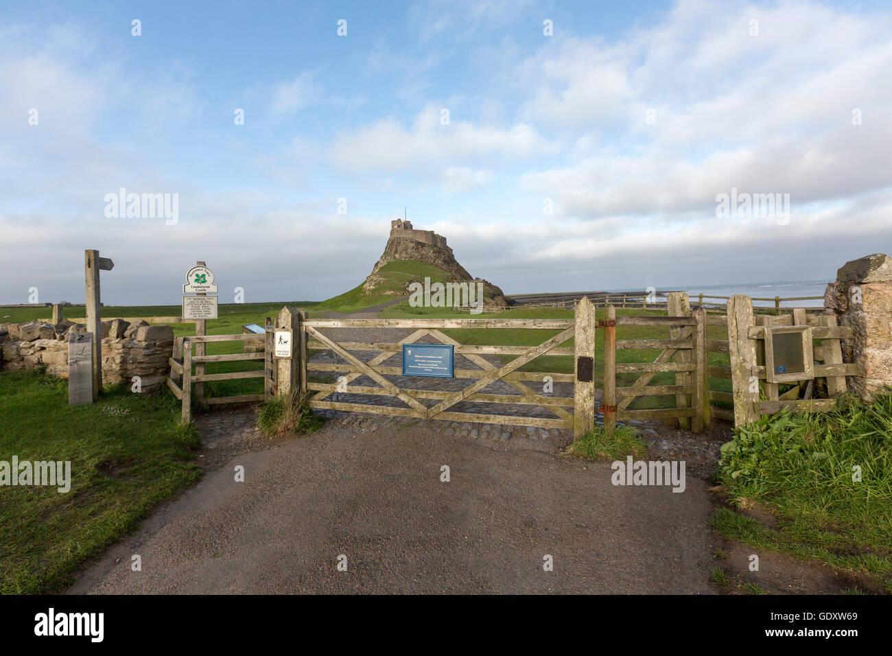 Field gate and ehe Holy Island of Lindisfarne castle, Northumberland, England, UK - Stock Image