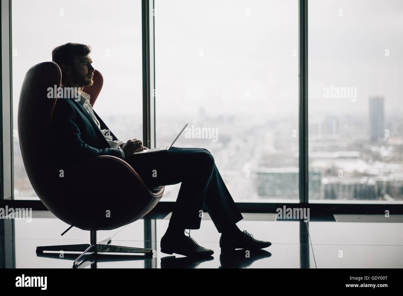Silhouette of young business man with laptop seated on a chair, winter city landscape - Stock Image