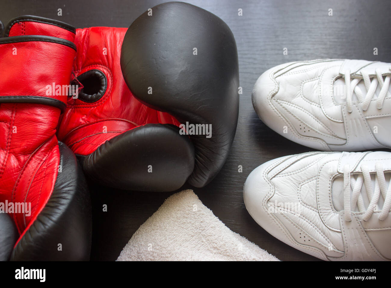 Boxing shoes, gloves and towel on black