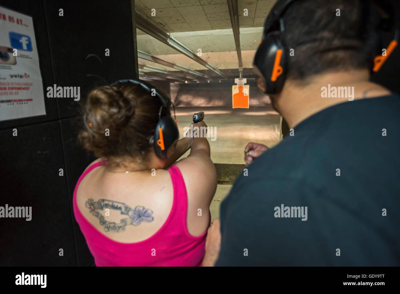 Las Vegas, Nevada - A woman fires her handgun at the Discount Firearms + Ammo indoor shooting range. - Stock Image