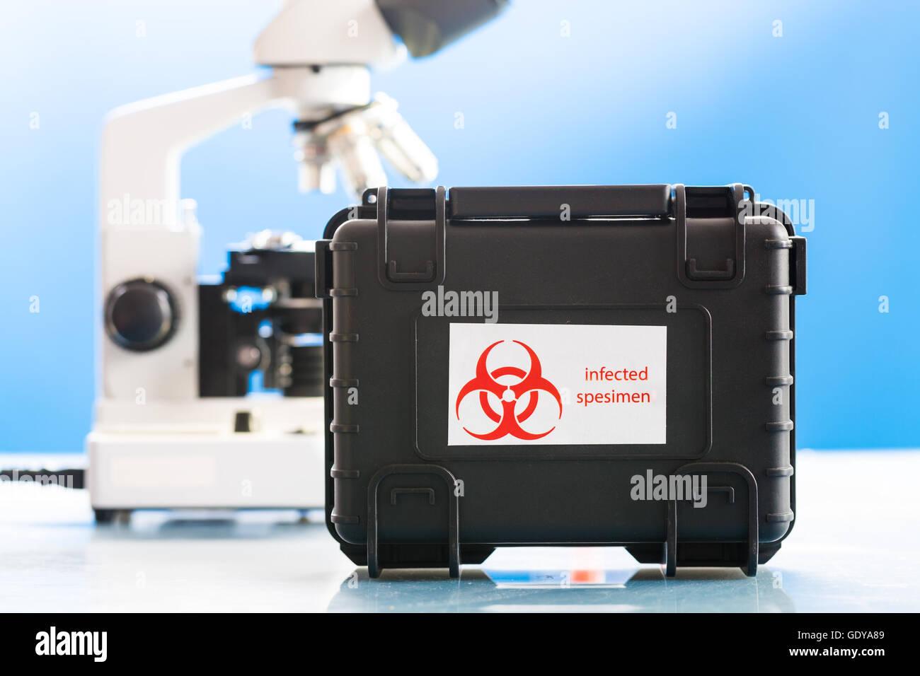 Safe case with epidemiologically dangerous viruses coronavirus and microscope in laboratory - Stock Image