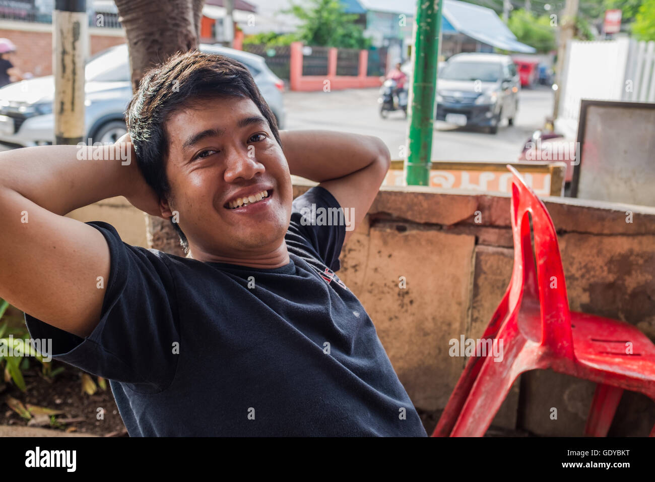 Local Thai man leaning back on chair with hands supporting head smiling,Chiang Mai,Thailand - Stock Image