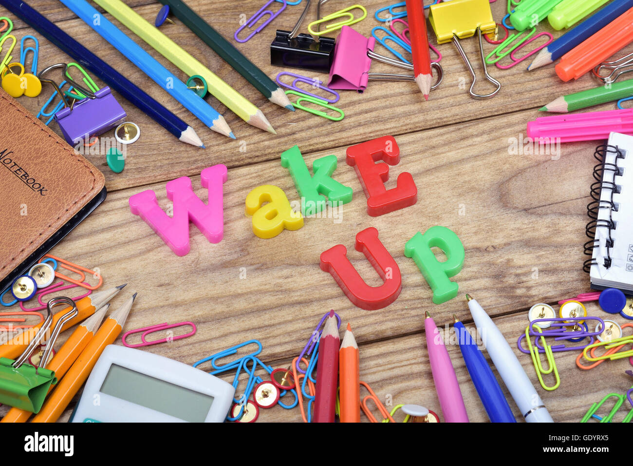 Wake up word and office tools on wooden table - Stock Image