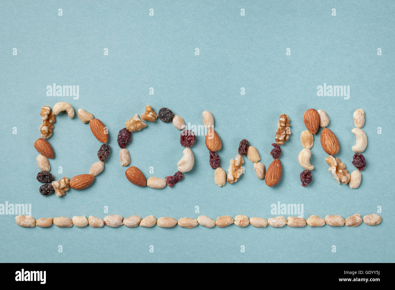 Typographical word of DOWN made of nuts - Stock Image