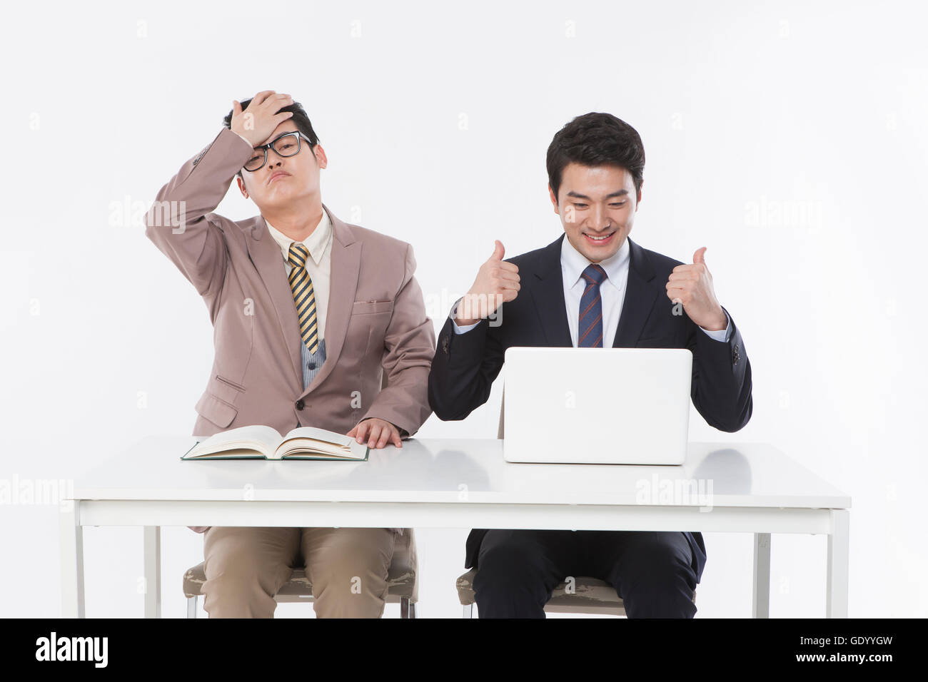 Contrast of two business men, one stressful with a book and the other successful with a notebook computer - Stock Image