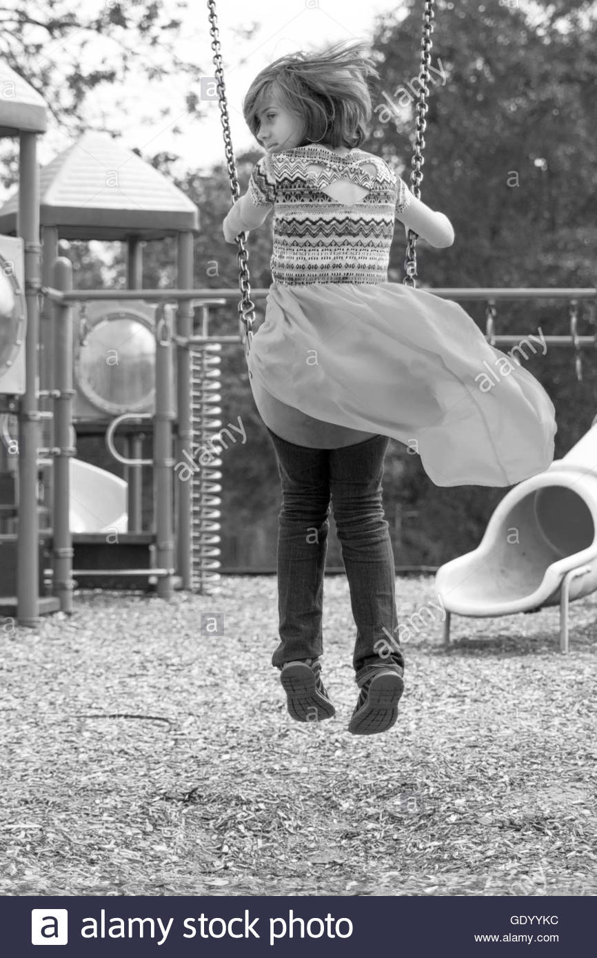 Girl swinging on a playground - Stock Image