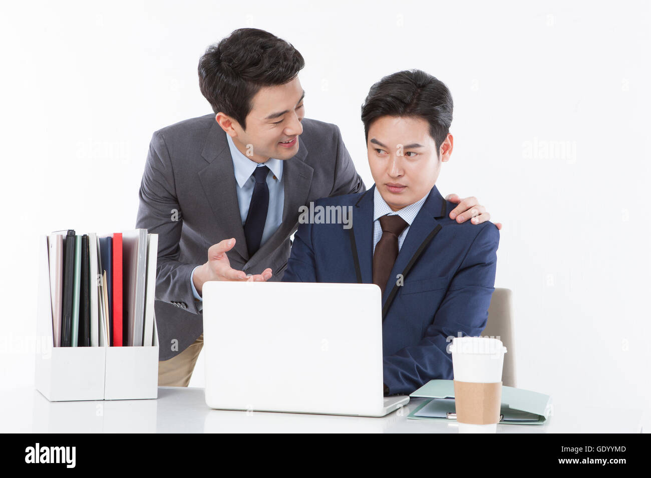 Portrait of two businessmen at work, one smiling and the other stressful at work - Stock Image