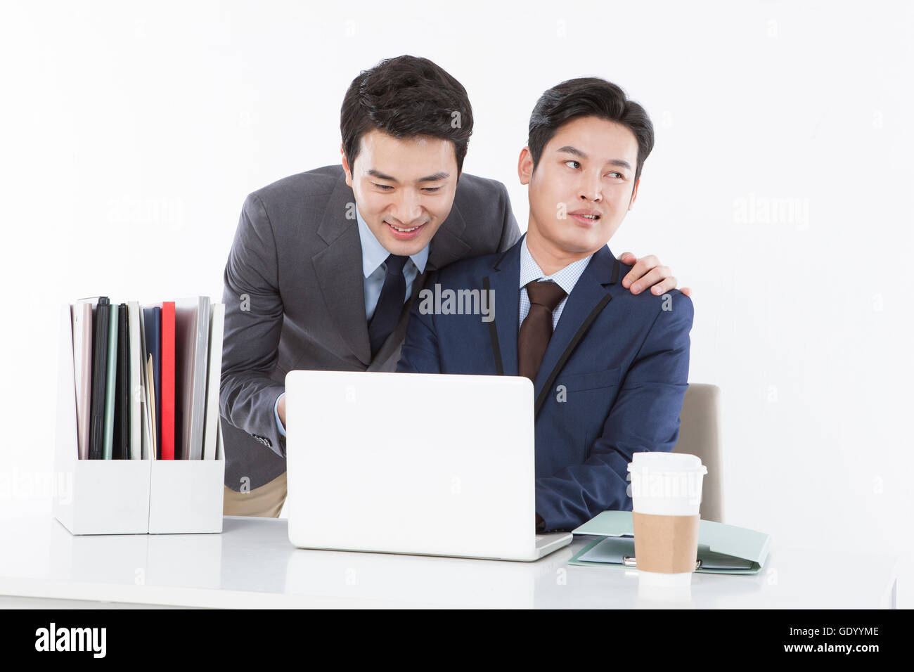 Contrast of two businessmen, one smiling and the other stressful at work - Stock Image