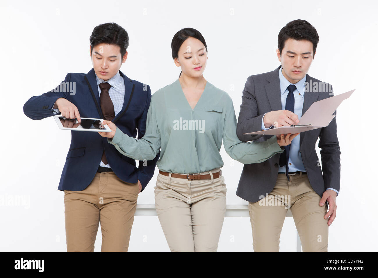Smiling business woman holds out a tablet and file to her coworkers and they touch them - Stock Image