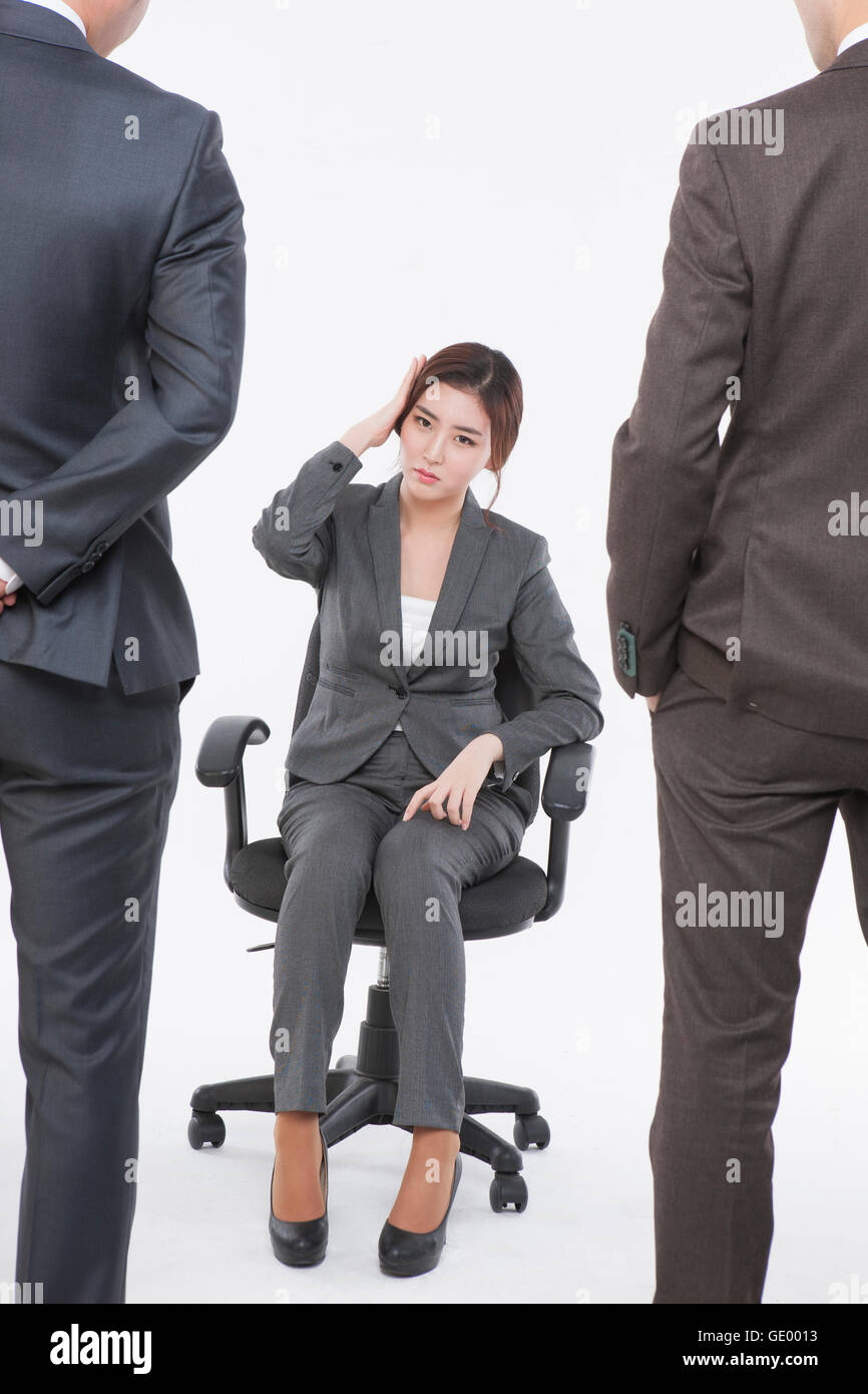 Stressful business woman sitting on chair and back of two business men standing in front of her - Stock Image