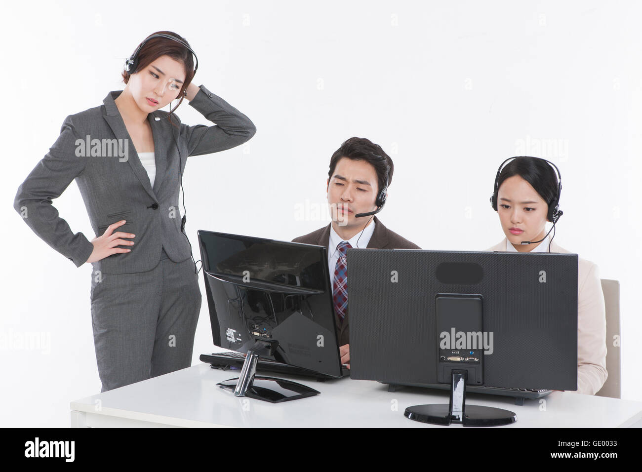 Three stressful business people at work - Stock Image