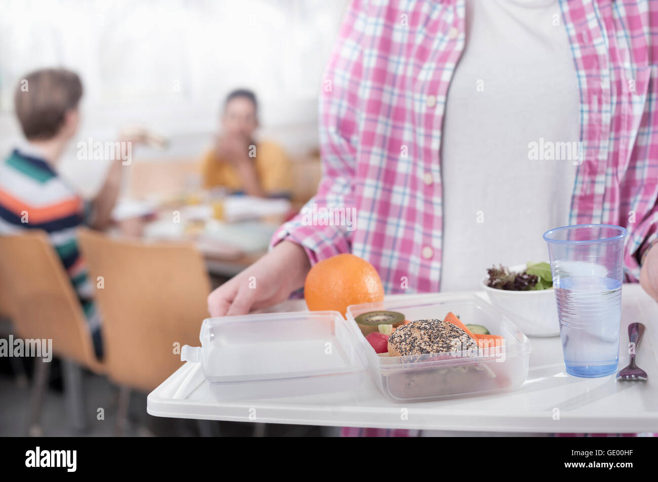 Midsection of a university student with lunch in canteen, Bavaria, Germany Stock Photo