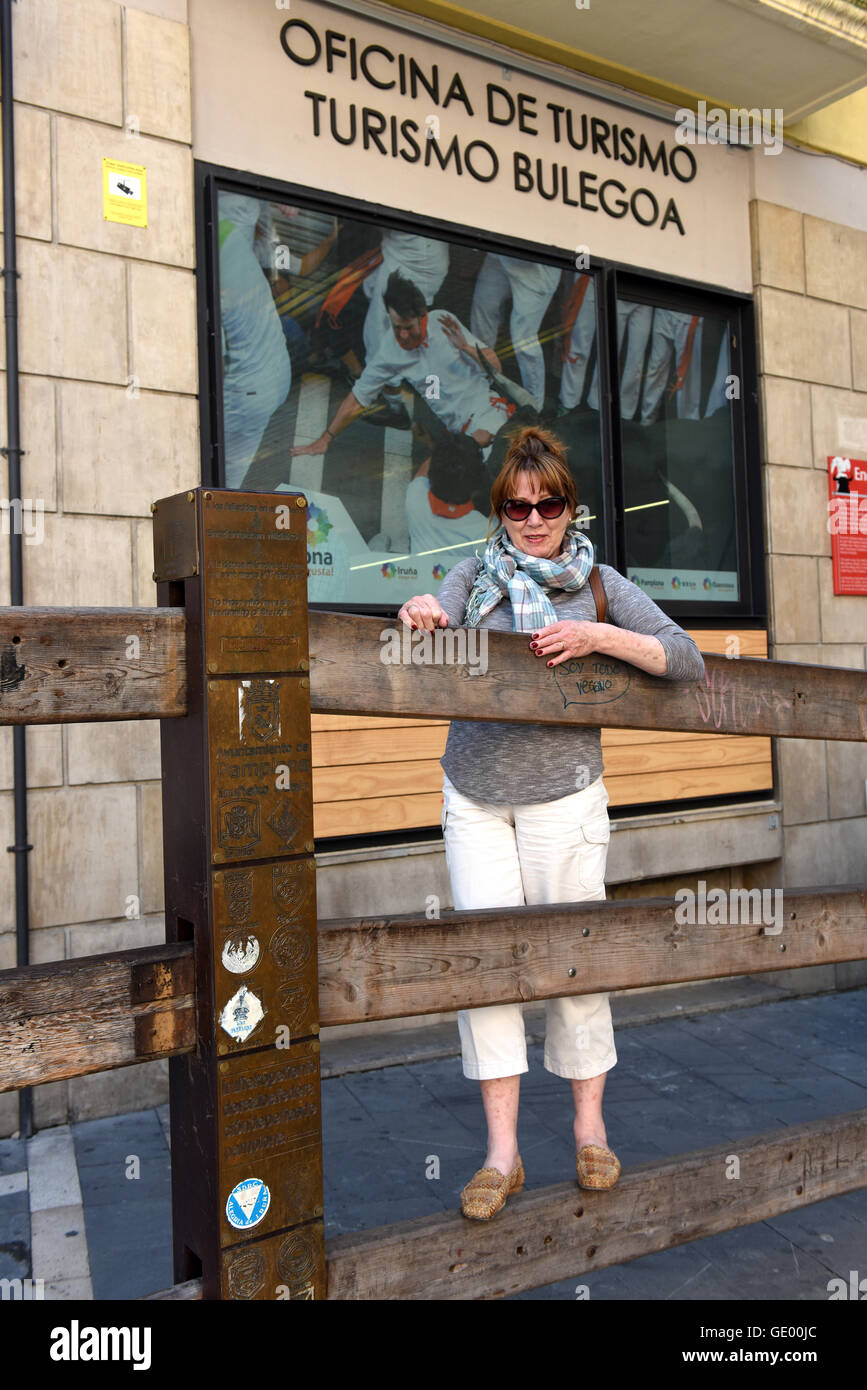 Tourist stand on wooden bull run rails outside tourism office in Pamplona Spain - Stock Image