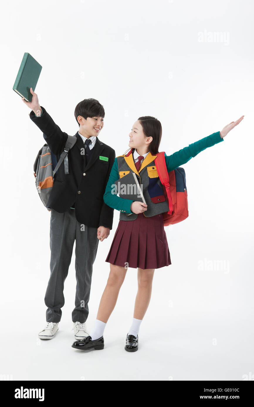 Smiling school boy and school girl with books standing face to face opening arms - Stock Image