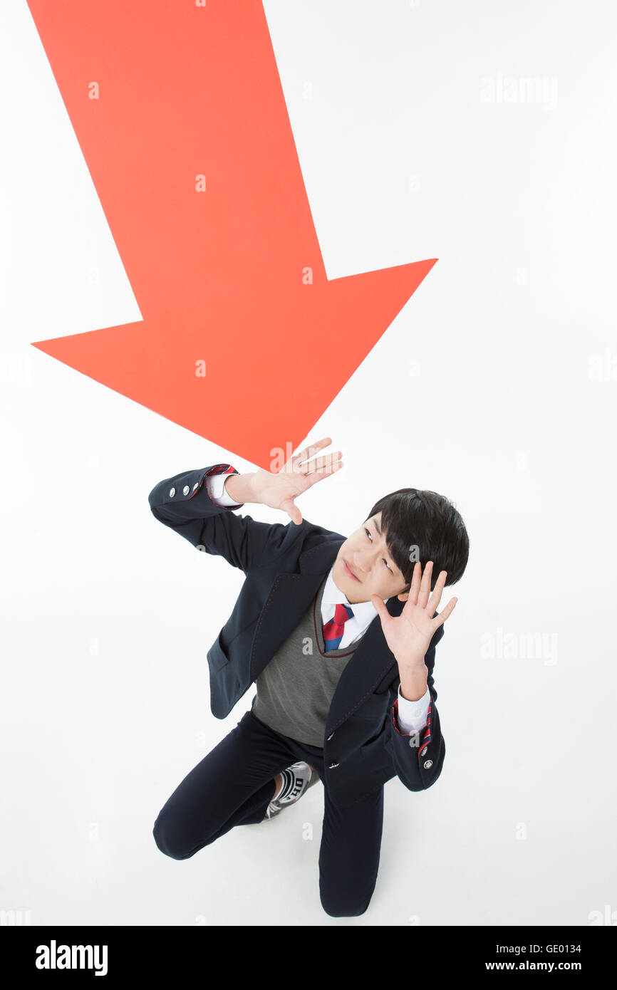 Stressful school boy blocking an arrow looking up - Stock Image