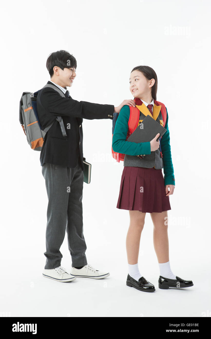 Smiling middle school boy and middle school girl walking with school bags and books - Stock Image