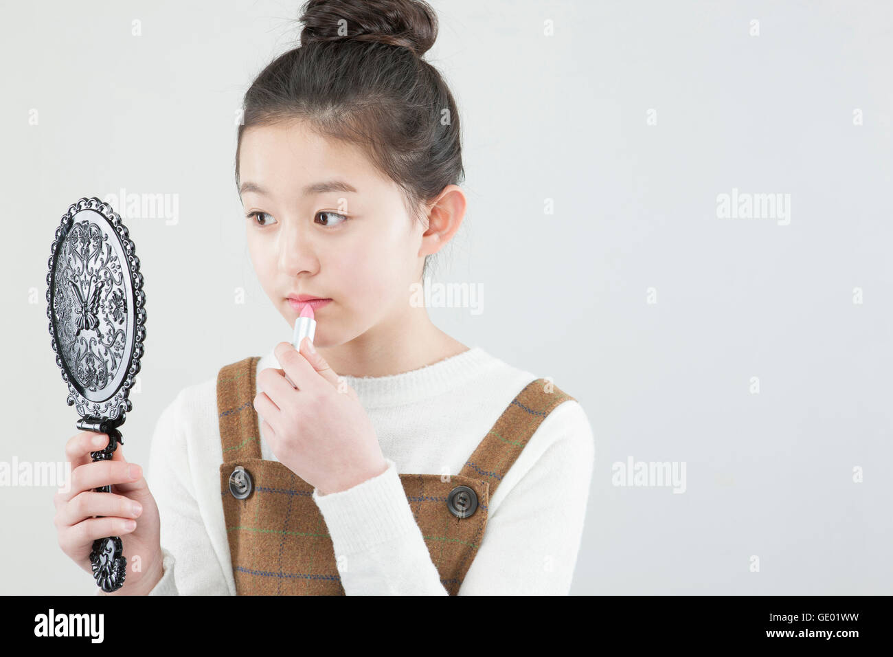 hand holding mirror. Side View Portrait Of Korea School Girl Holding A Hand Mirror And Putting  On Make- T