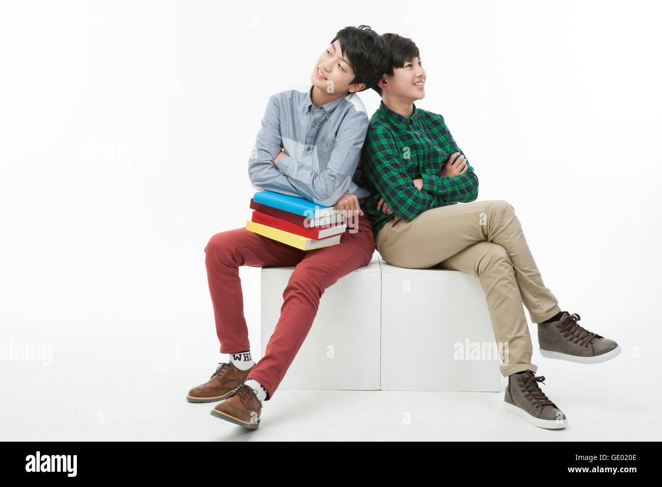 Two Korean school boys in casual clothes sitting with books