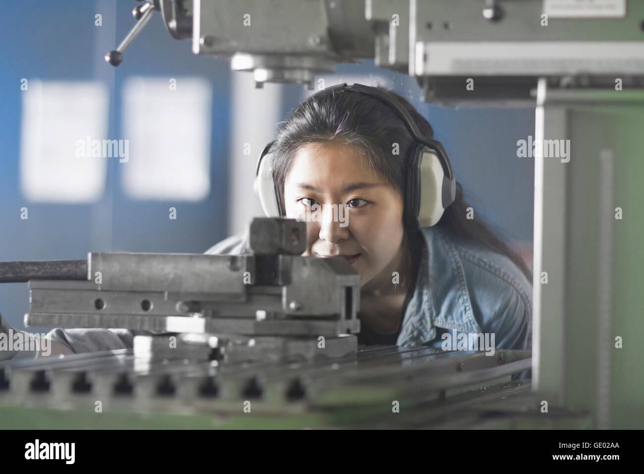 Young female engineer wearing headphones and working in an industrial plant, Freiburg im Breisgau, Baden-Württemberg, Stock Photo
