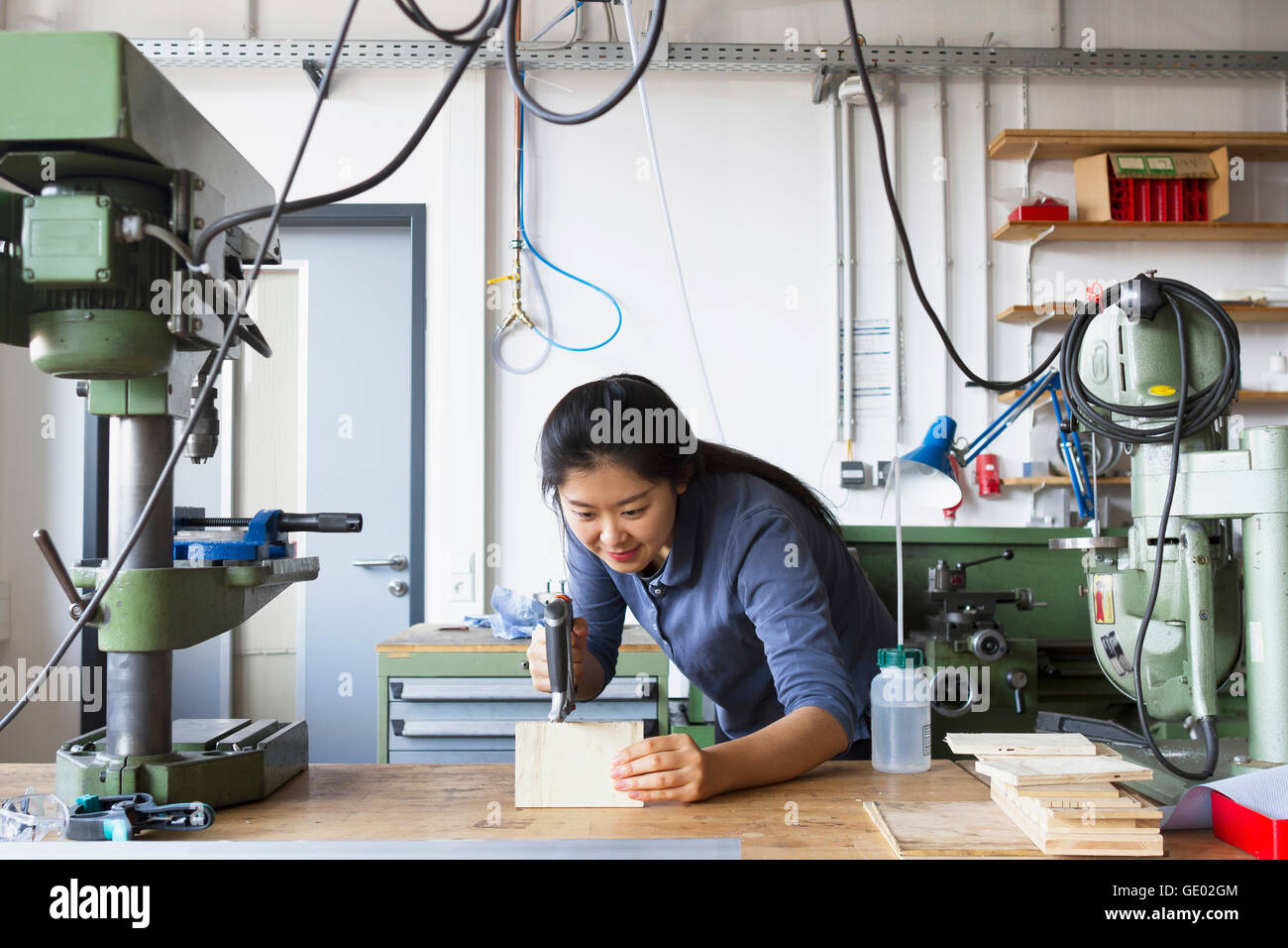 Young female carpenter sawing a piece of wood in an industrial plant, Freiburg im Breisgau, Baden-Württemberg, - Stock Image