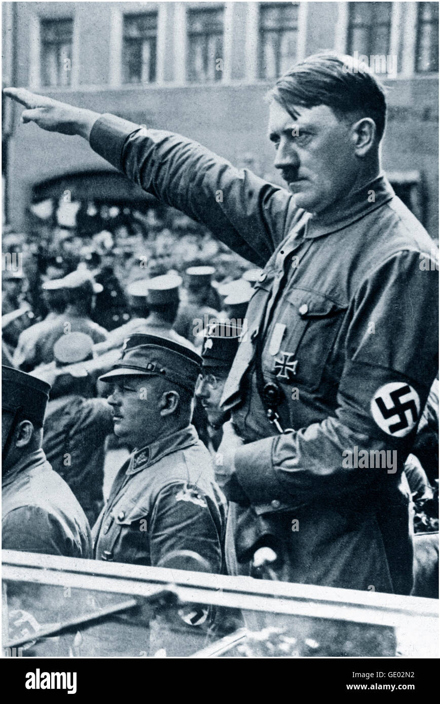 Adolf Hitler in open car wearing swastika armband performing Nazi salute at a political rally parade in Germany - Stock Image