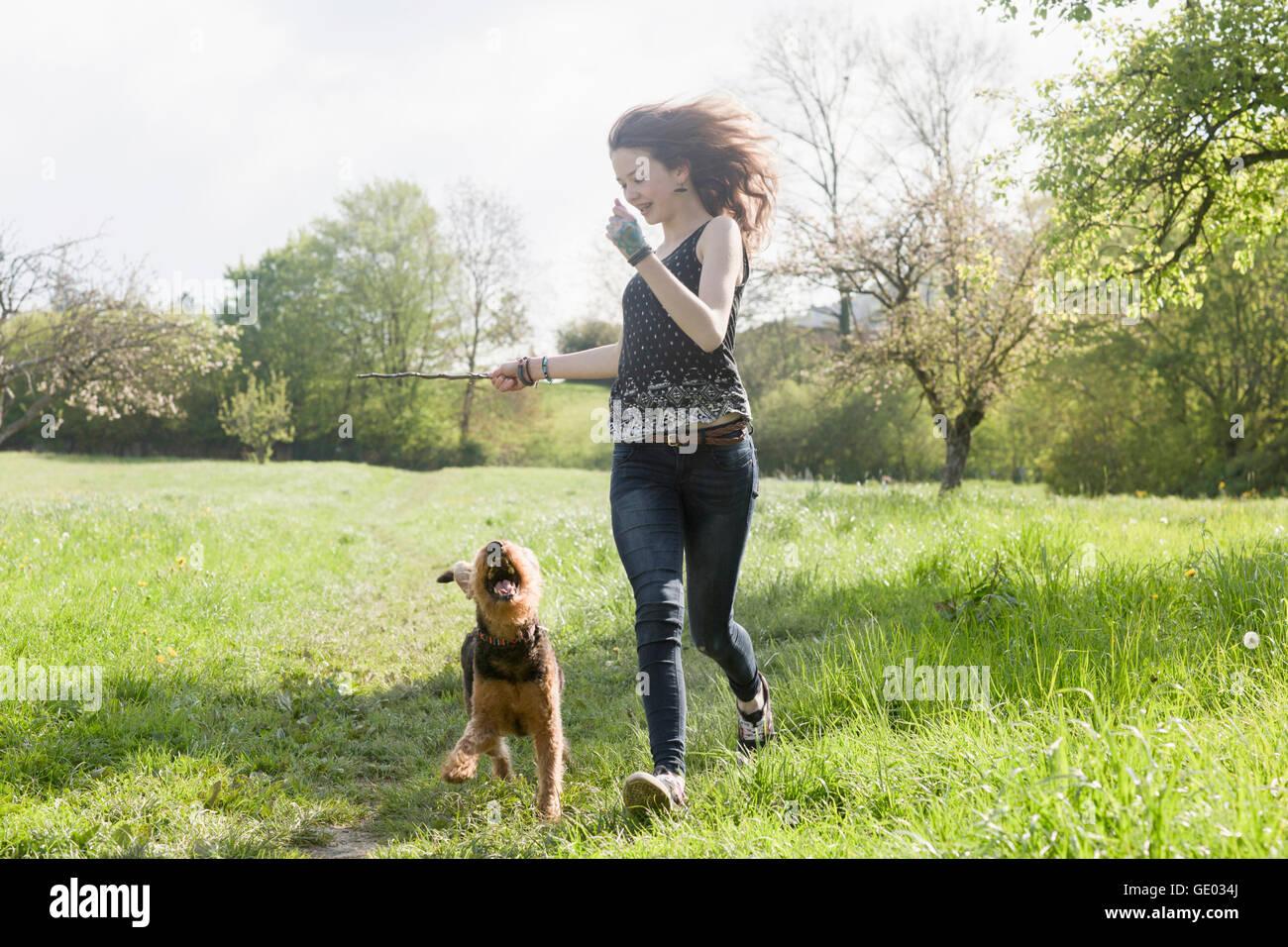 Teenage girl running in park with her dog, Freiburg im Breisgau, Baden-Württemberg, Germany - Stock Image