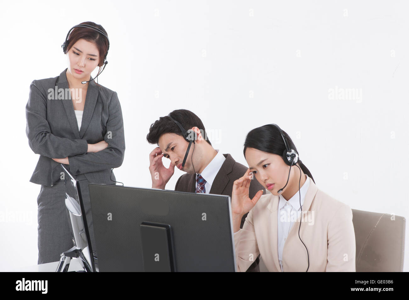 Three young stressful business people wearing headphones - Stock Image