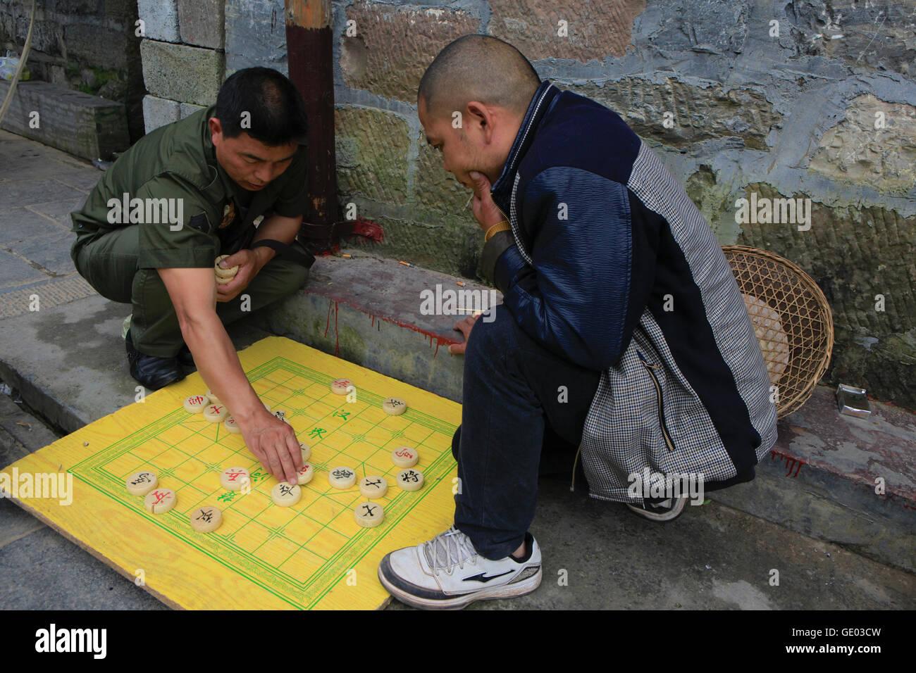 Two men playing  Chinese chess at Fenghuang , Hunan China - Stock Image