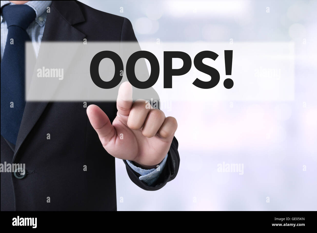 OOPS! Businessman hands touching on virtual screen and blurred city background - Stock Image