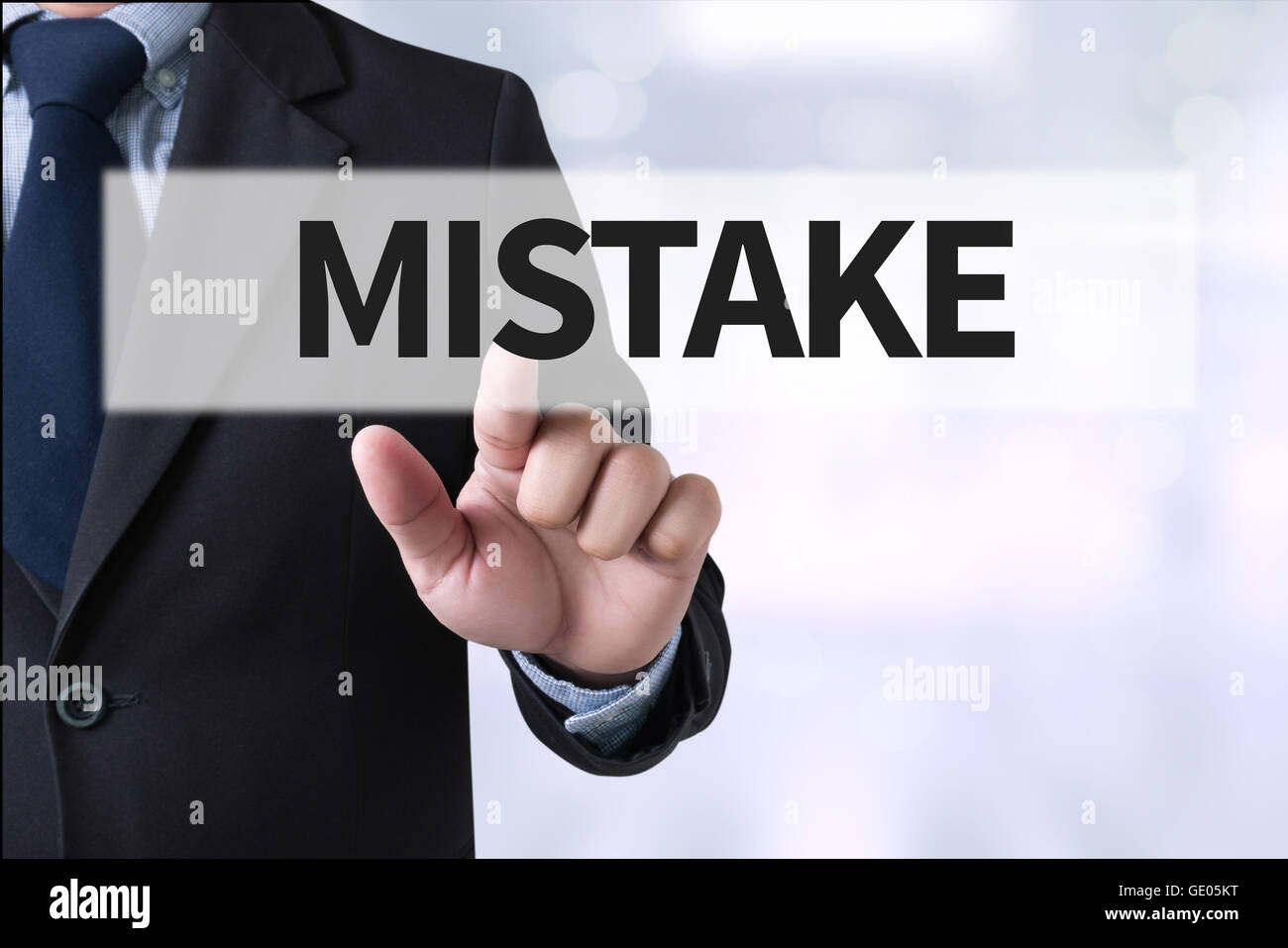 MISTAKE Businessman hands touching on virtual screen and blurred city background - Stock Image