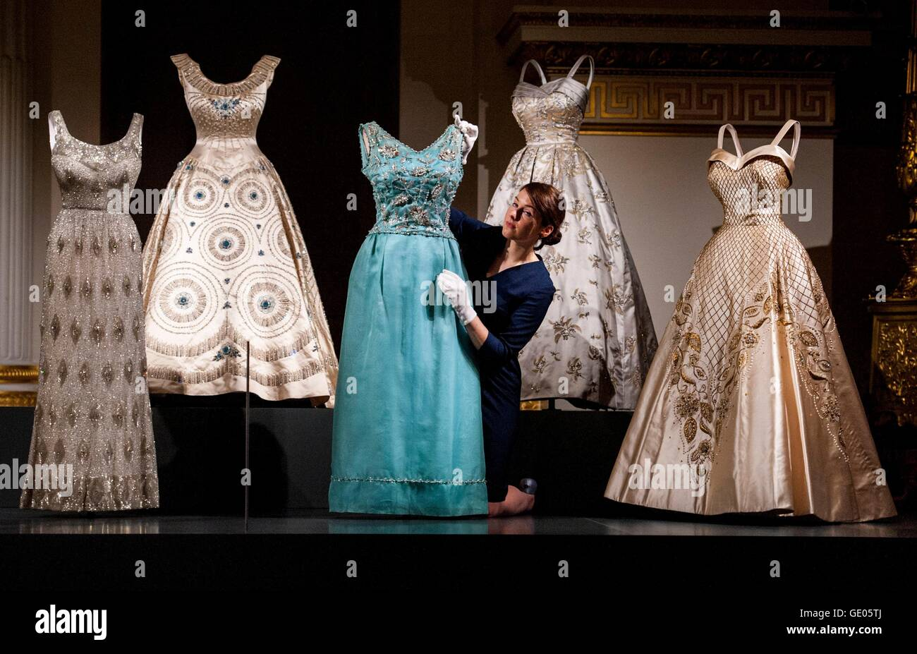 A member of staff adjusts a selection of evening gowns worn by Queen ...